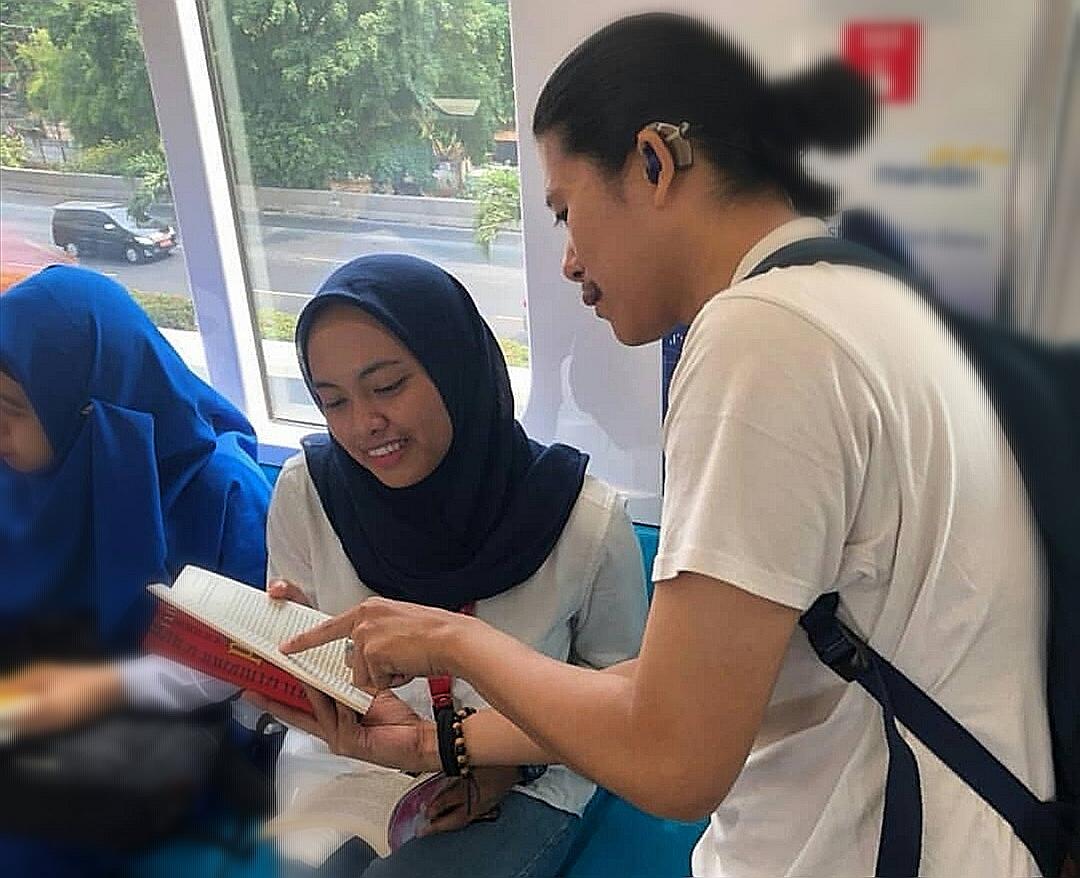 Salah satu Teman tuli sedang menunjukkan buku yang ia baca ke relawan non-disabilitas